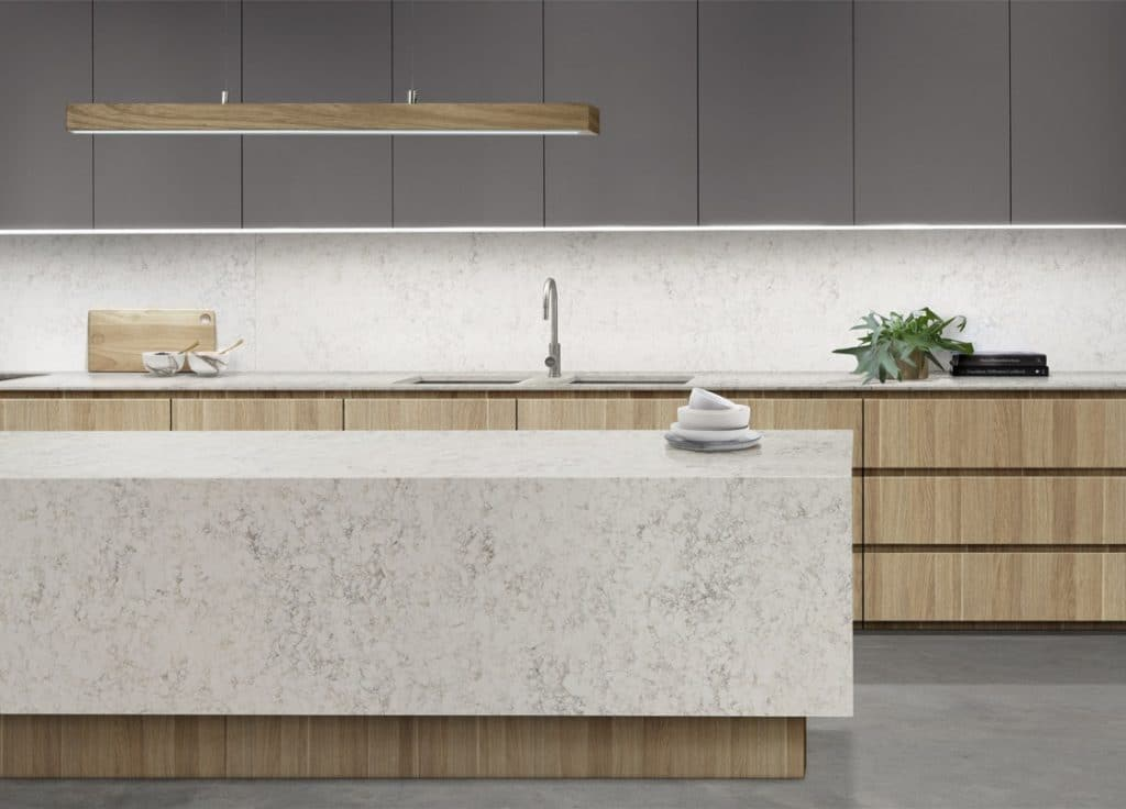 A custom kitchen with timber draws, essastone benchtop, dark grey overhead doors. Natural finishes and clean lines.