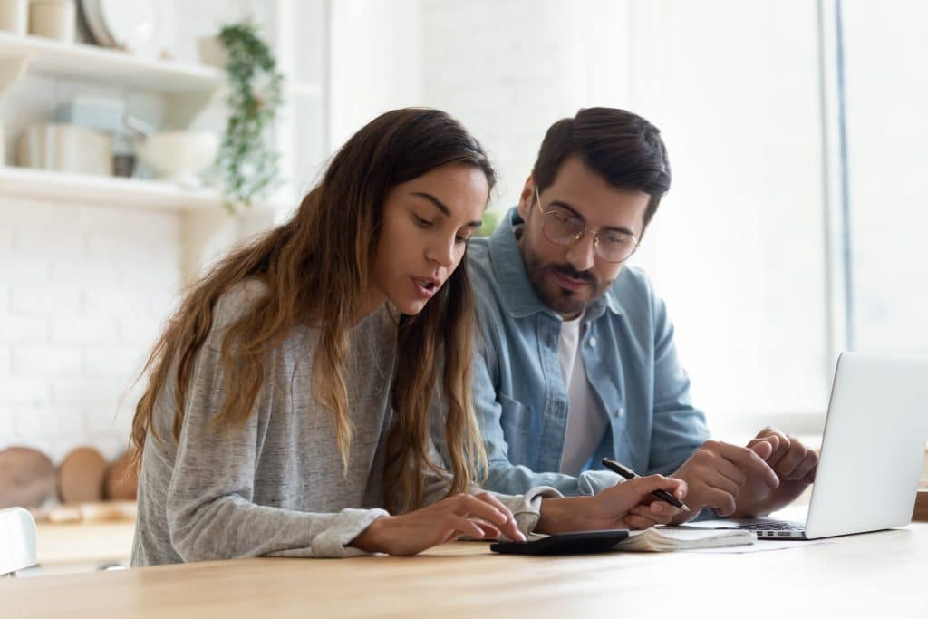 A young couple sit at a laptop on the kitchen bench planning their renovation budget with a calculator.