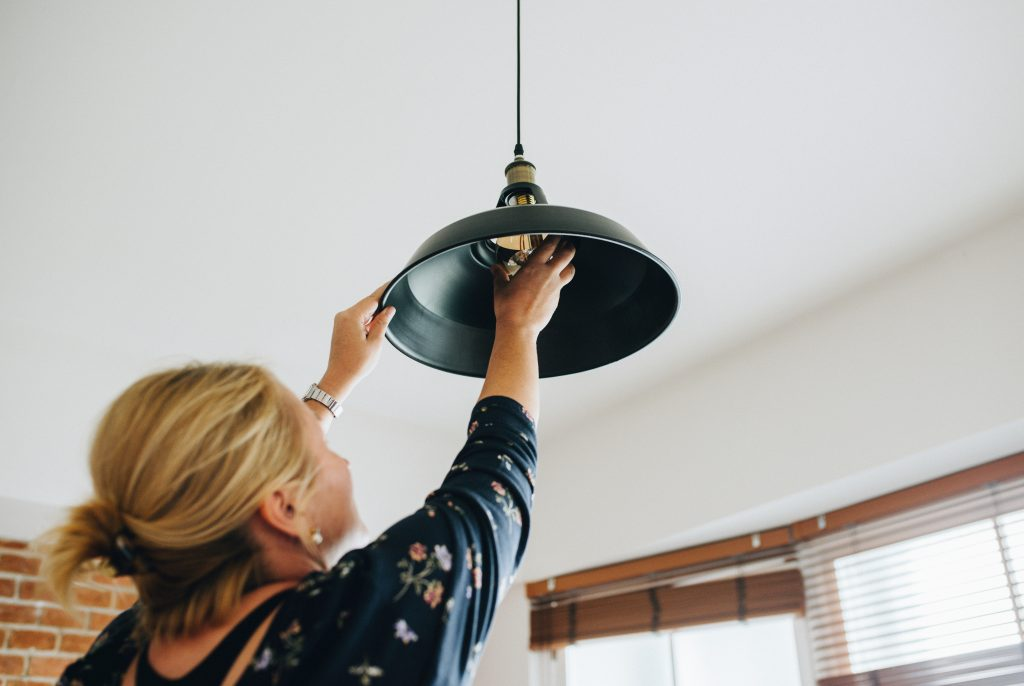 A woman changes a light bulb in her kitchen to prepare for resale.