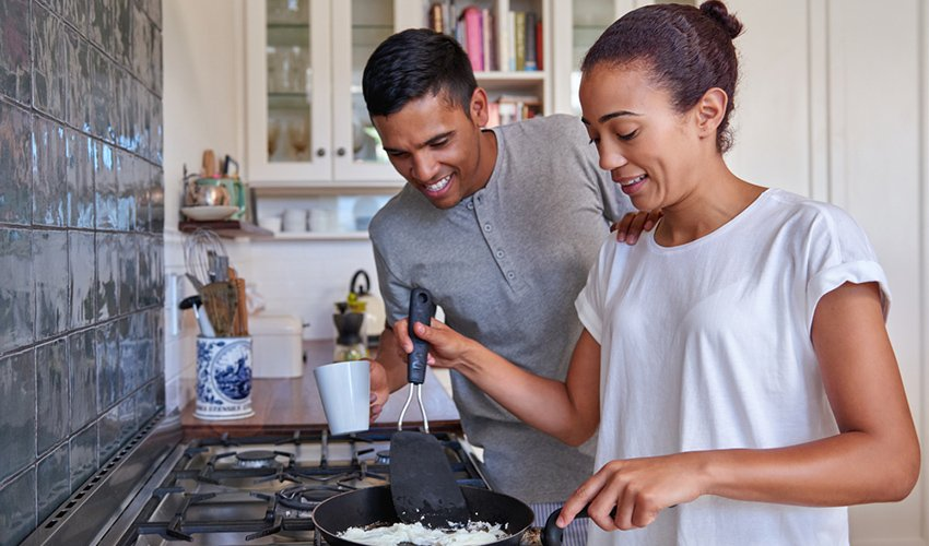 couple cooking eggs in kitchen