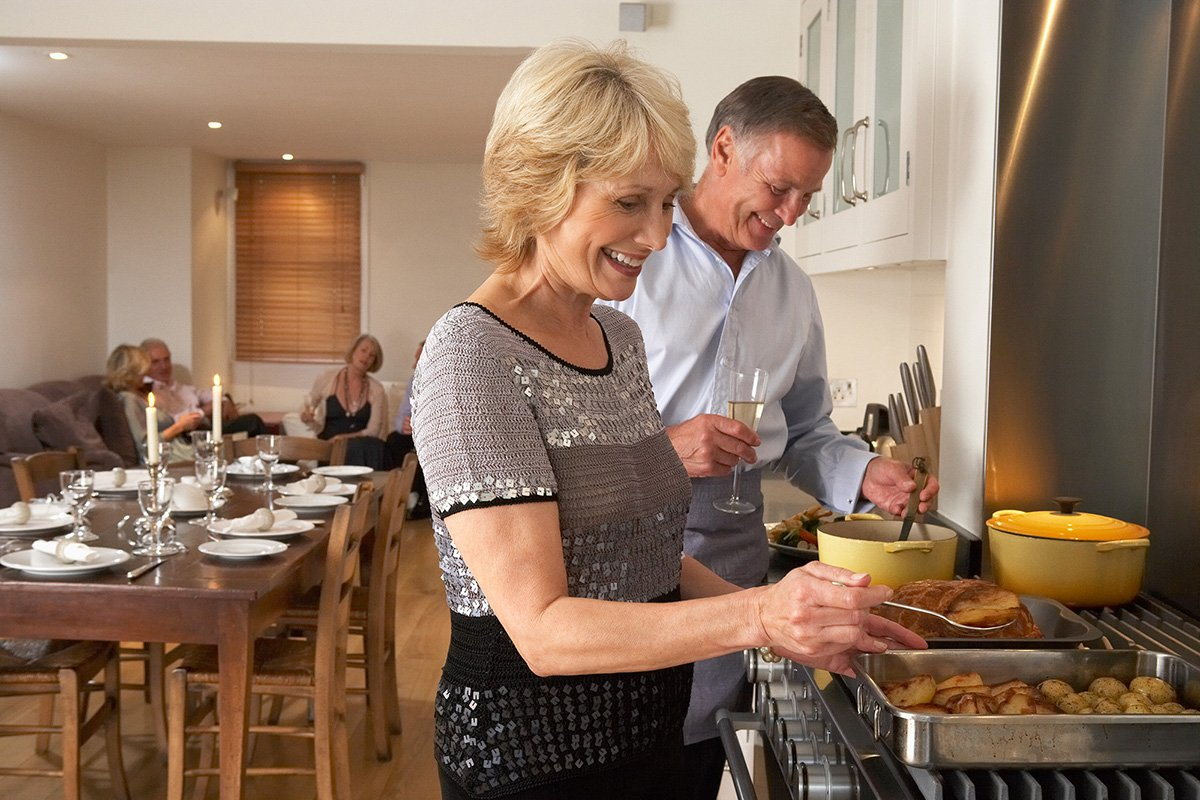 middle aged couple entertaining friends in the kitchen cooking